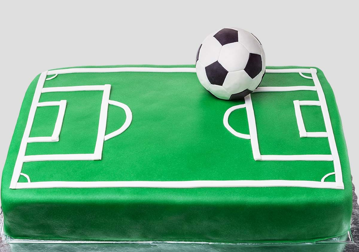 A football pitch cake with an icing football on the top.