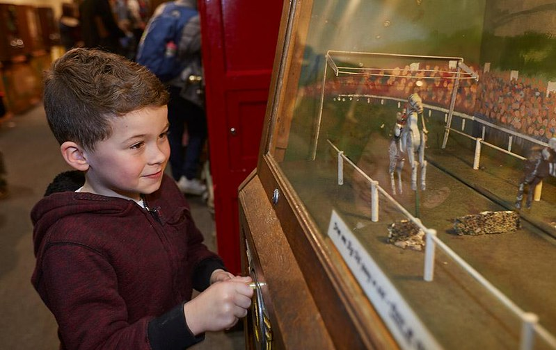 Young boy looking at a Victorian figurine set.