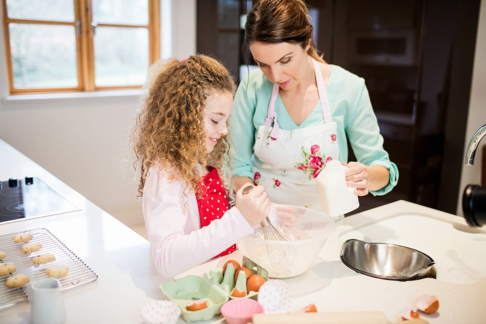 A mother and daughter baking a pizza cake together in the kitchen.