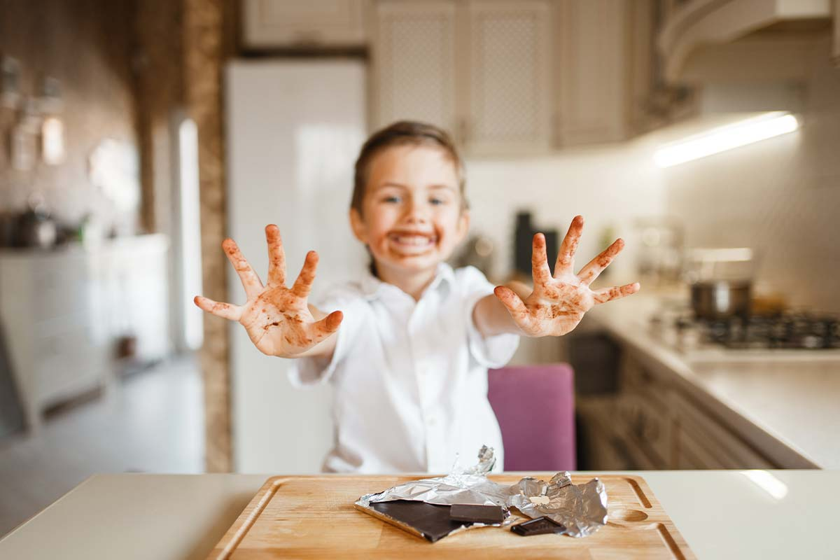 Little girl in the kitchen holding her hands out in front of her showing the chocolate on them and around her mouth too.