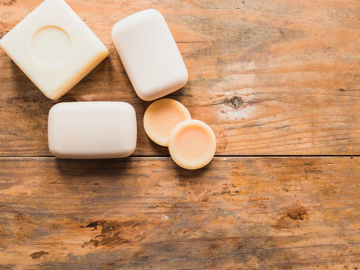 Bars of soap, all different shapes and sizes, for kids on a wooden table.