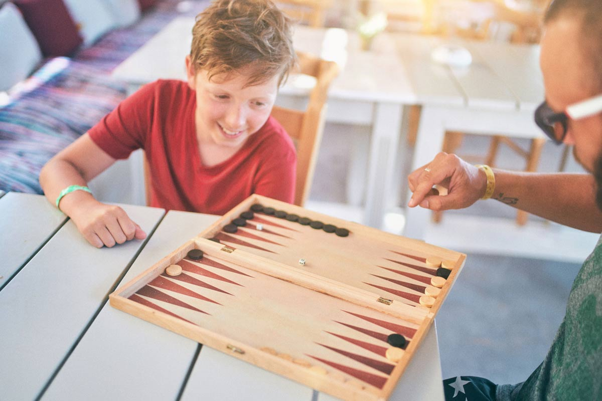 Teenage boy sat at a table outside playing backgammon with his dad.