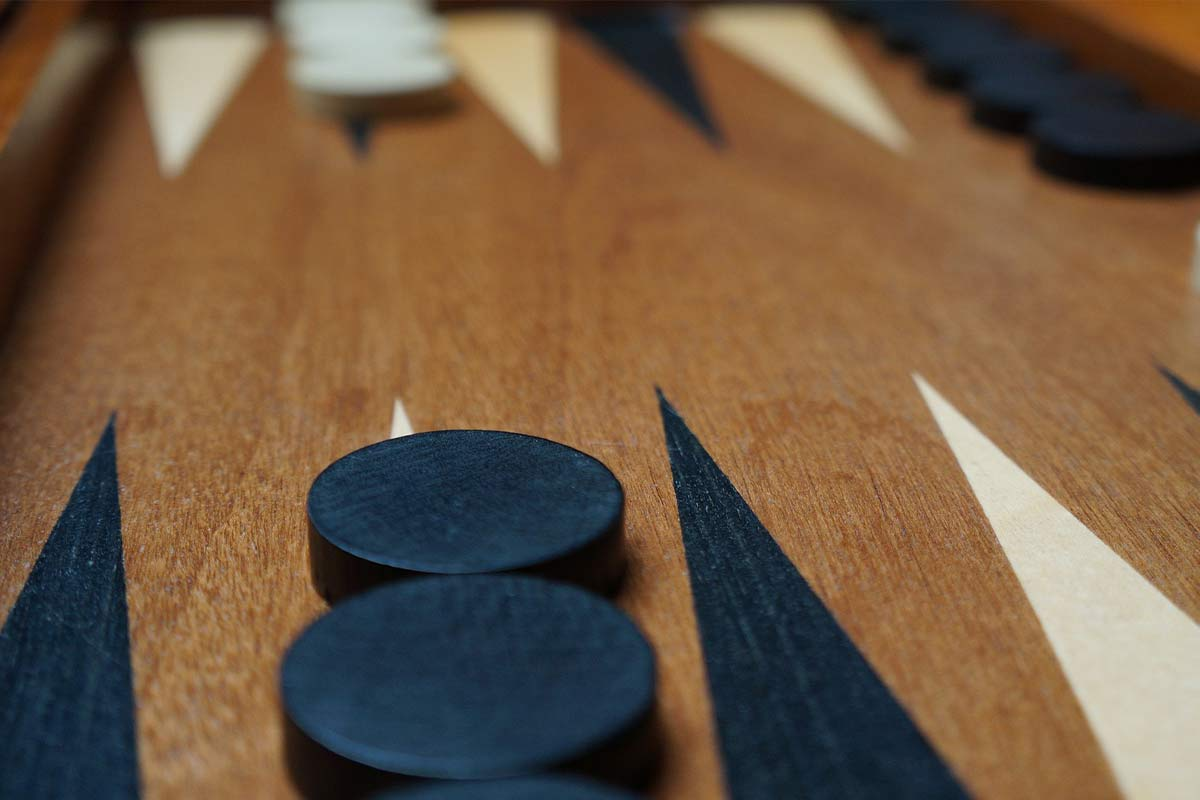 Close up of the backgammon board and the checkers on it.