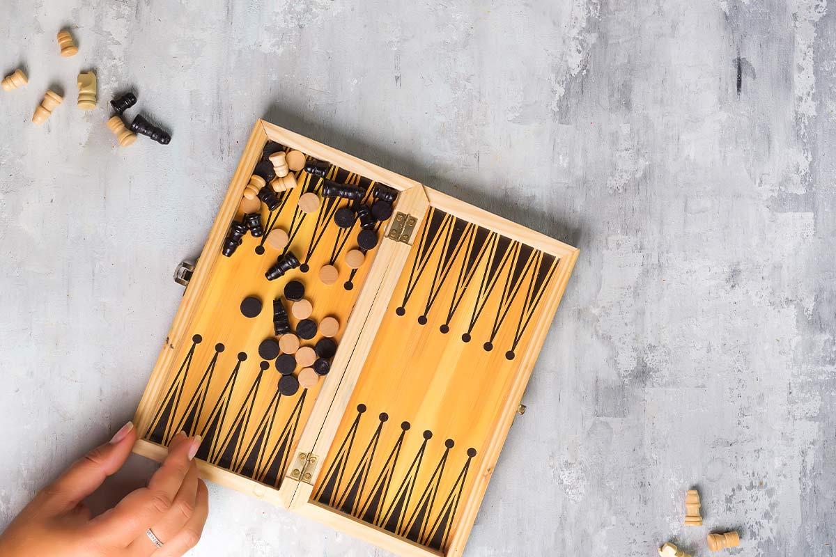 Hand resting on the corner of a small backgammon board.