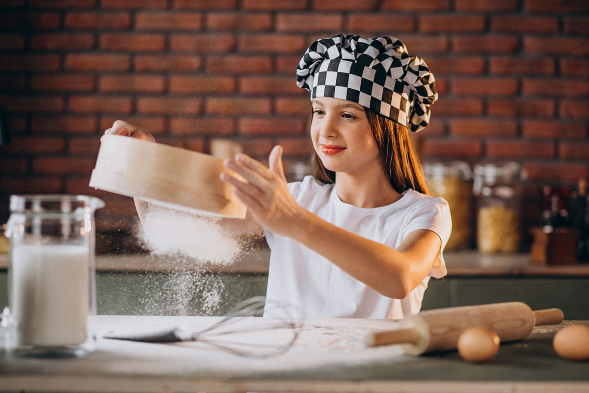 Teenage girl wearing a chef's hat, sifting flour in the kitchen to make a laptop cake.