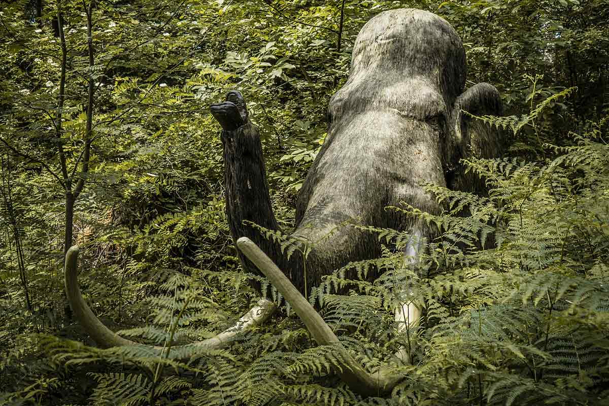 The head of a model of a large stone age animal emerging from greenery, it has a long trunk and two white tusks.