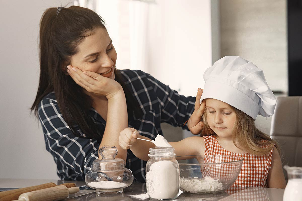 Mother smiles at daughter wearing a chef hat as she weighs flour to make a cow cake.