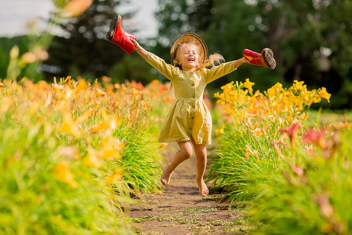 A happy young girl in a yellow dress runs through a field of yellow flowers holding wellies in her hands.