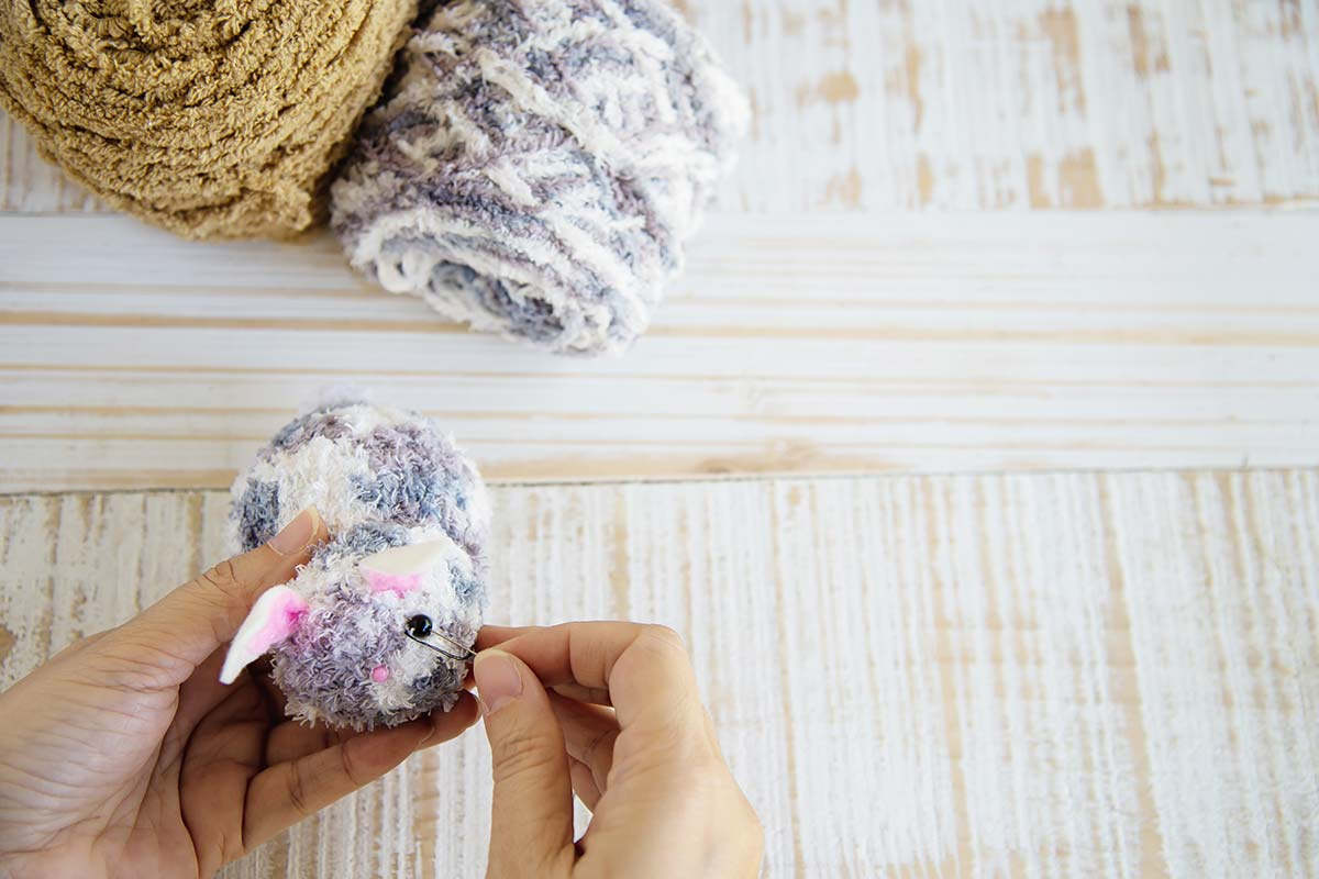 Close up of a person fastening a safety pin to some thread to make a pom pom key ring.