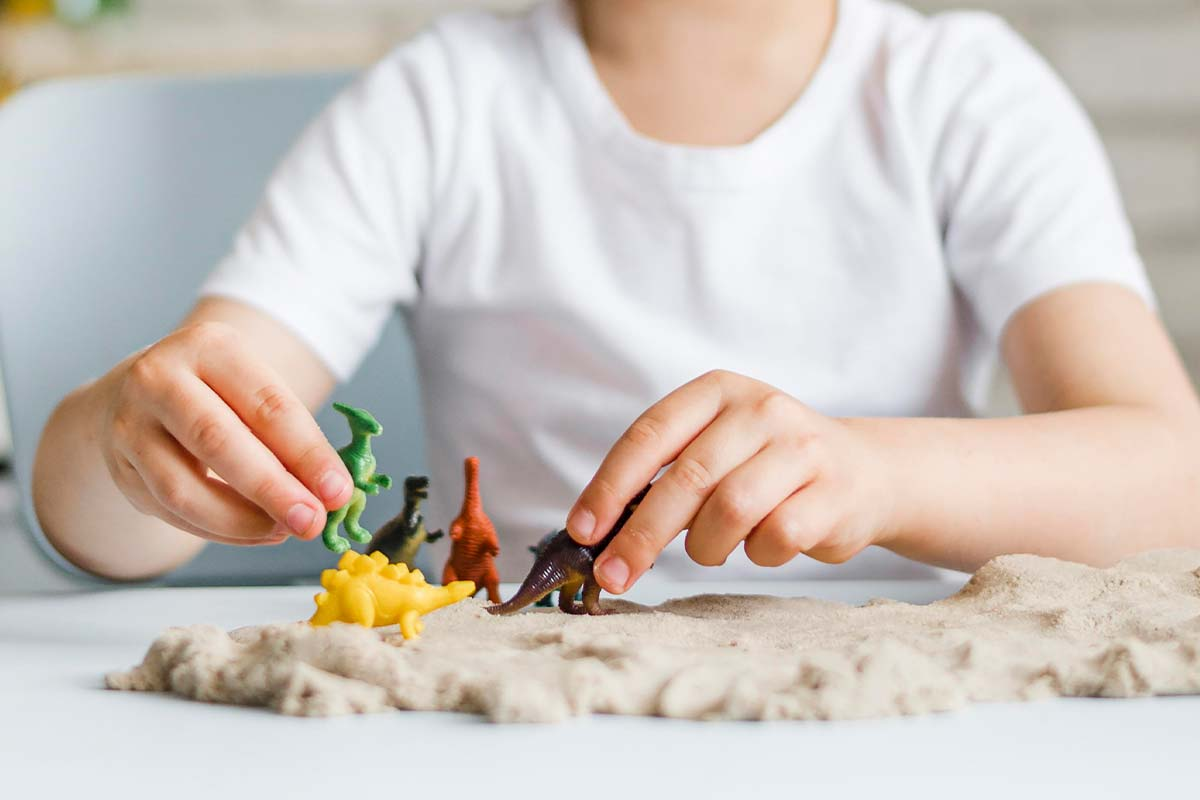 Young boy playing with dinosaur toys which he can use when making his own key ring.