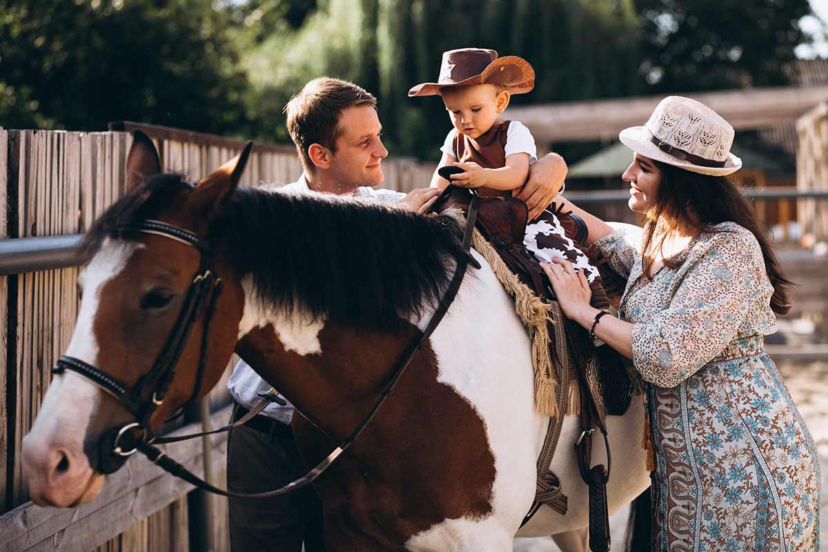A young boy wearing a cowboy hat rides a brown and white horse whilst his parents support him from either side.