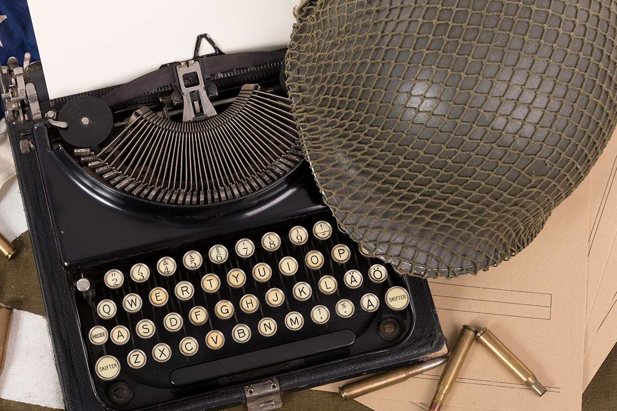 An old-fashioned typewriter with a helmet perched next to it.
