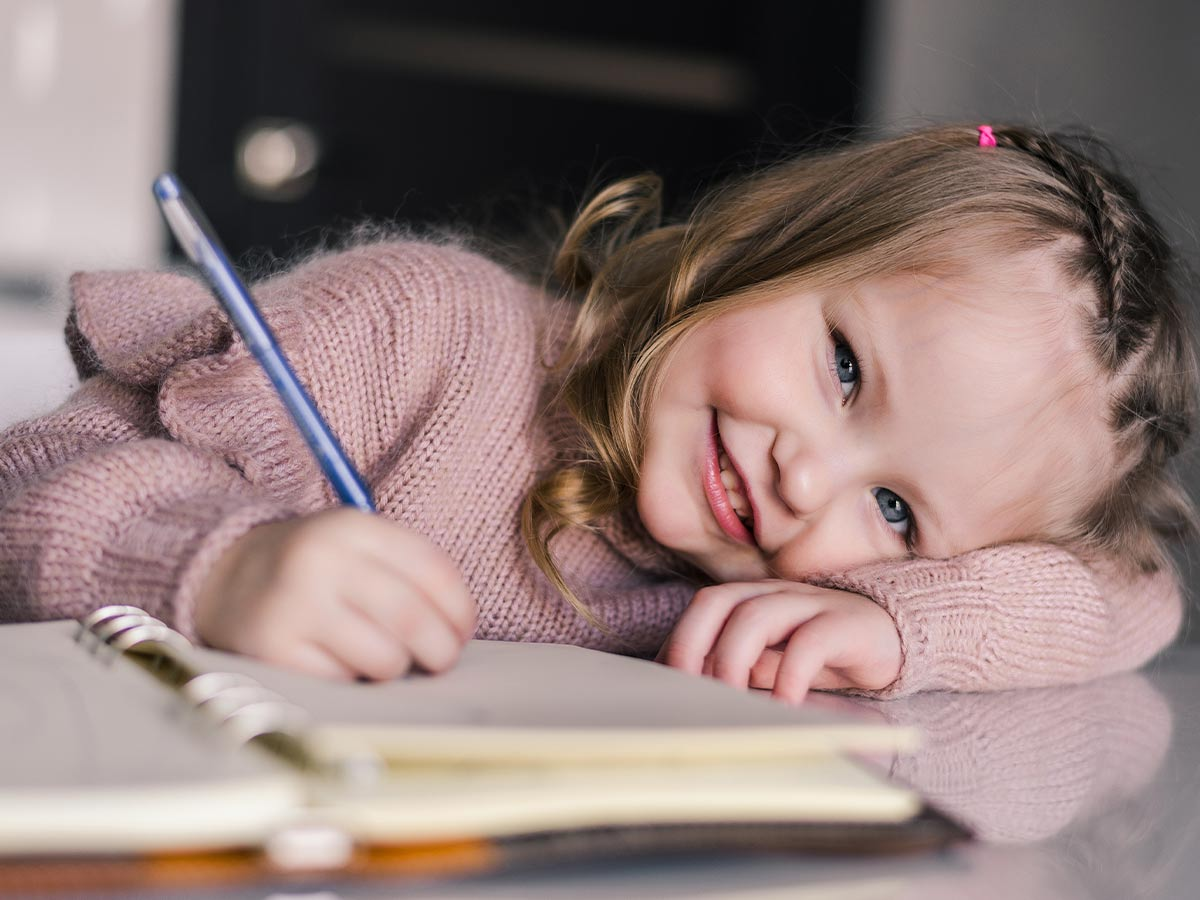 A little girl writing in a notebook looks up and smiles at the camera.