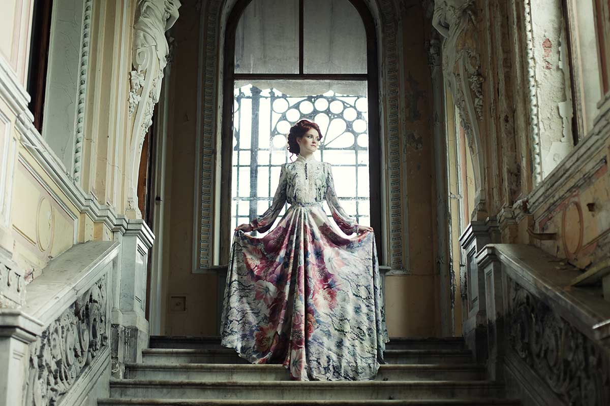 An expensively dressed Victorian woman standing at the top of a wide staircase in her house.