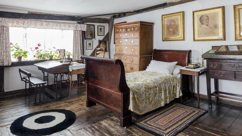 A modest Victorian bedroom with wooden furnishings and some pictures on the wall.o
