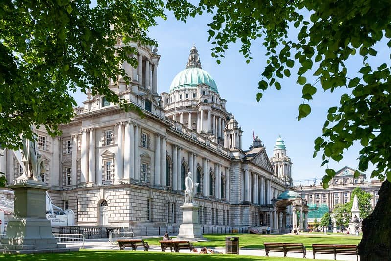 Belfast Town Hall on a sunny day with trees in the foreground.
