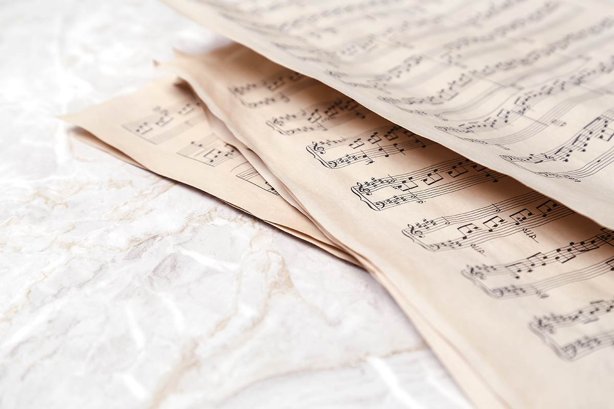 Sheets of music on a white marble surface.