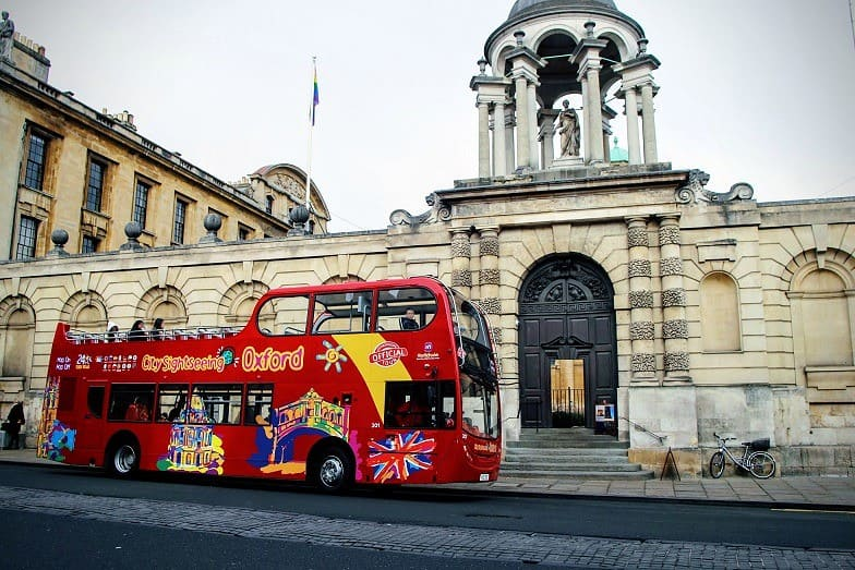 An open-top sightseeing bus standing outside one of Oxford's colleges.