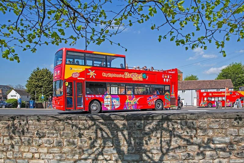 A red open-deck City Sightseeing tour bus in Stratford-upon-Avon.