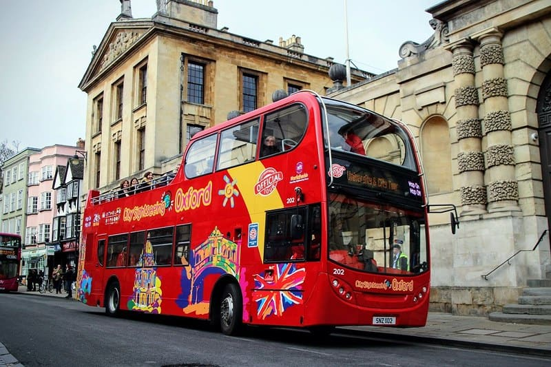 An open-top double-decker sightseeing bus standing in a street in Oxford.