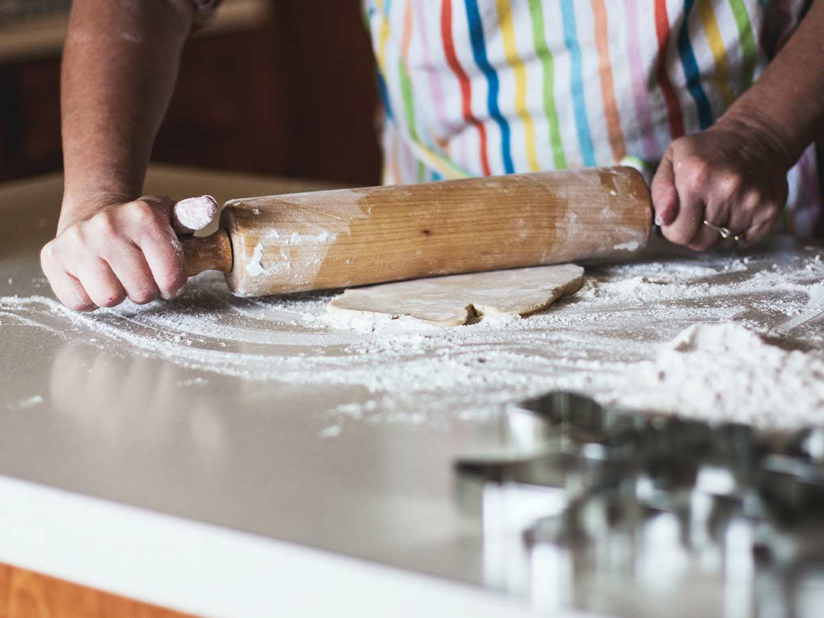 Close up of a large rolling pin being used by someone in a stripey rainbow coloured apron to roll out icing to make a pug cake.