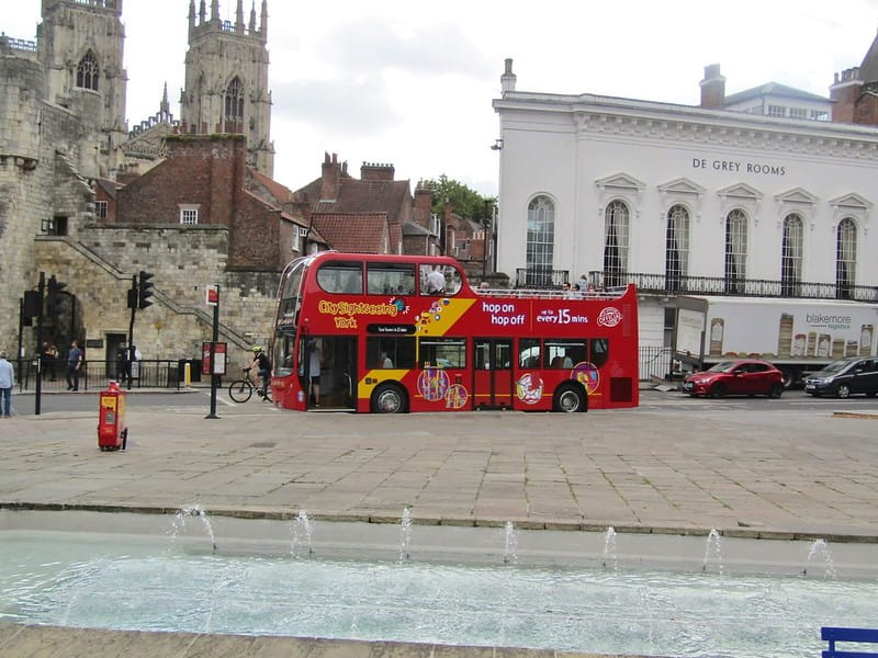 An open-top sightseeing bus parked in York city centre.