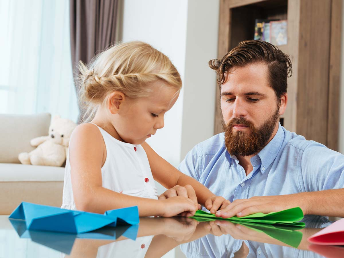 Little girl sat at the table making DIY flower wreaths with her dad.