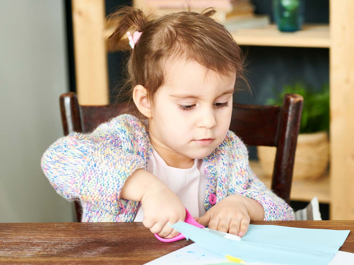 Little girl sat at the table cutting paper to make a DIY flower wreath.
