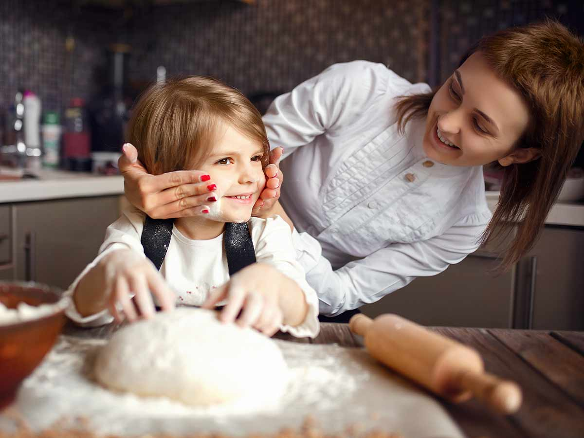Mum rubbing flour on her son's face while they're in the kitchen baking a Postman Pat cake.