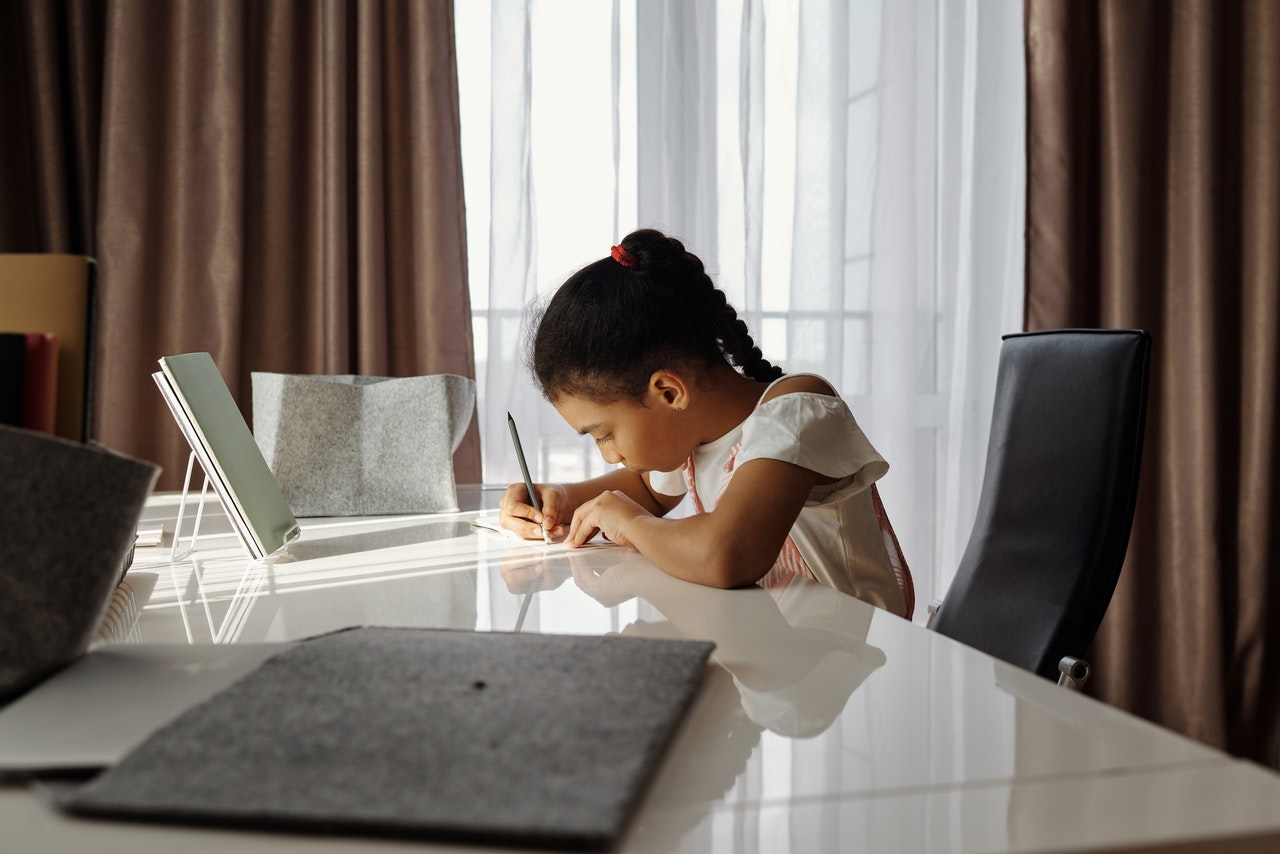 A young girl is sitting at her desk, writing and practising using idioms.