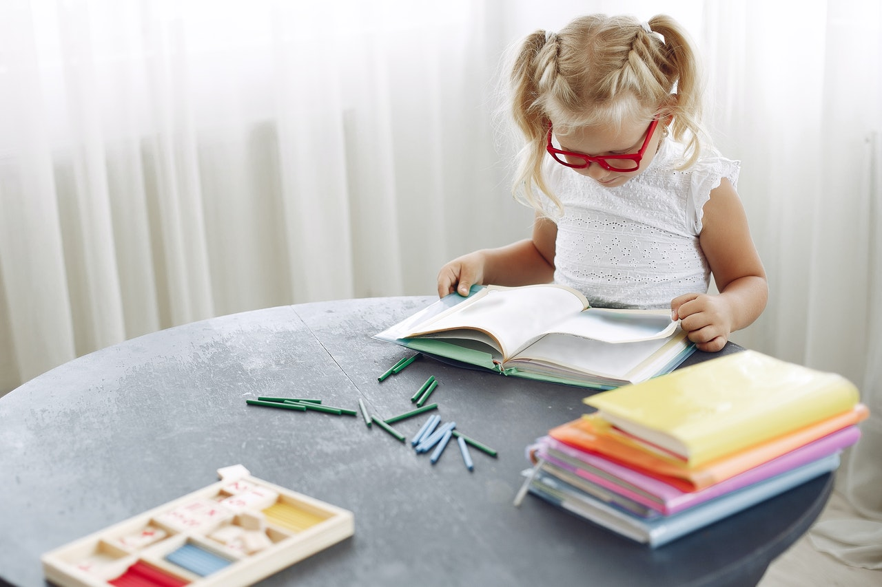A young girl wearing red classes is sitting at the table, surrounded by colourful books, learning about idioms.