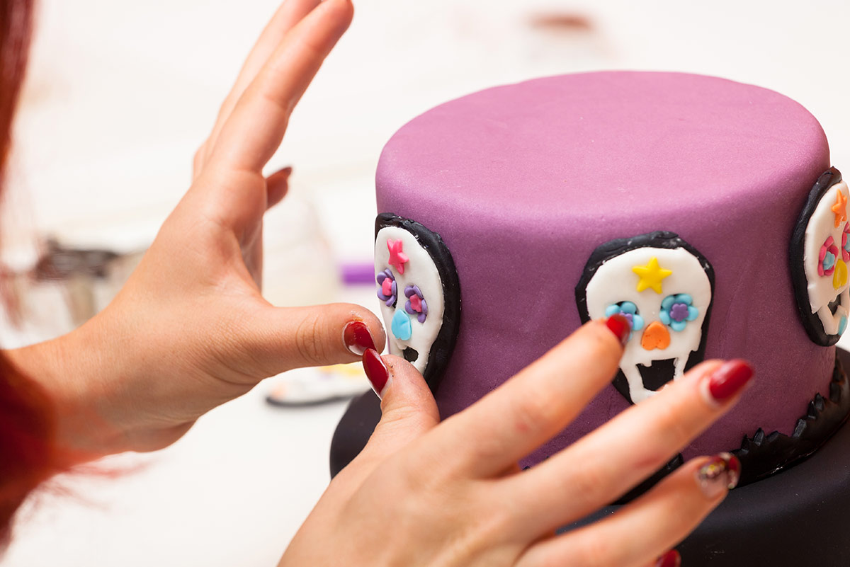 Close up of woman's hands as she sticks skull icing decorations on the side of a purple pirate birthday cake.