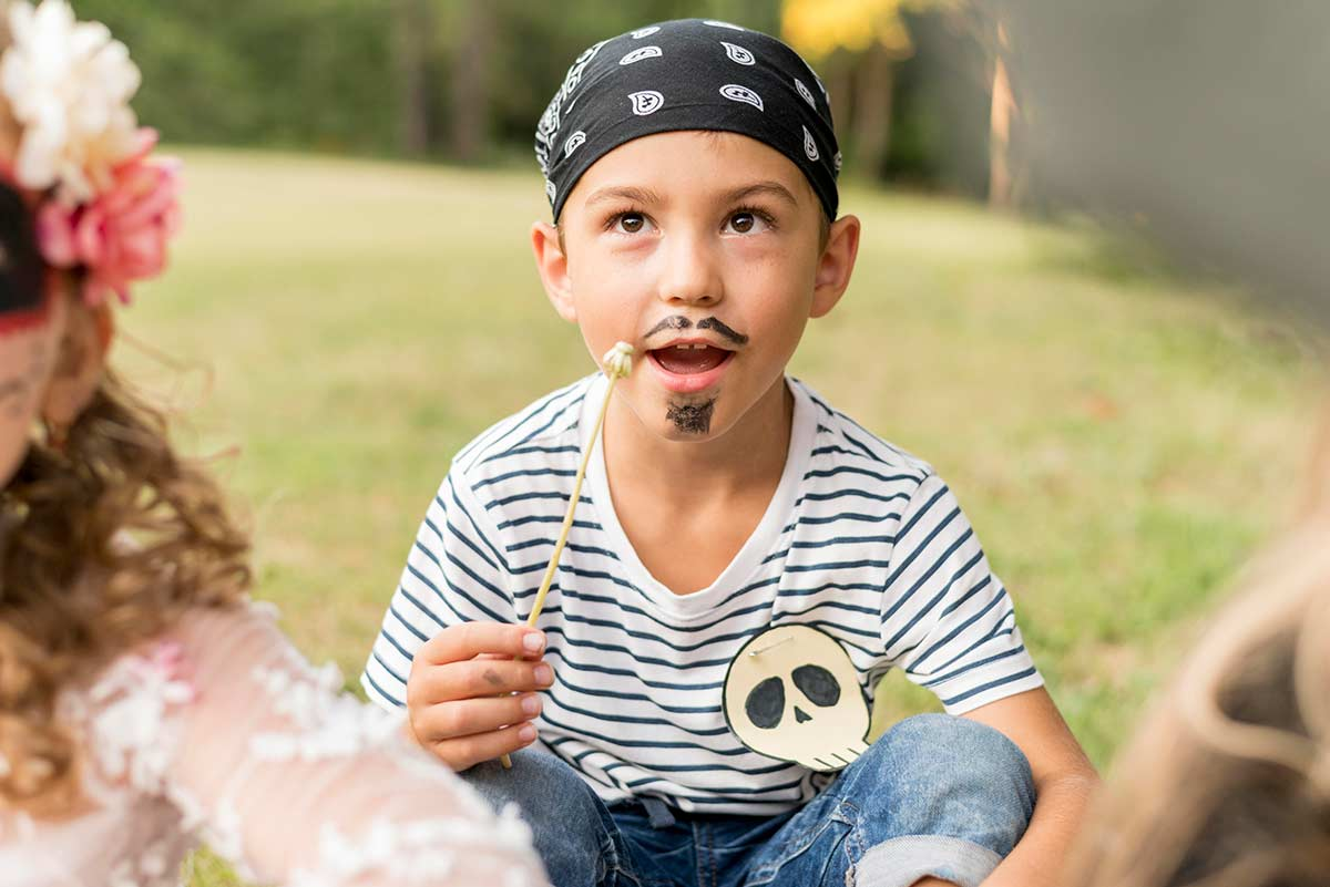 Boy dressed as a pirate, with a moustache and goatee drawn on and a bandana on his head, sat on the floor outside.