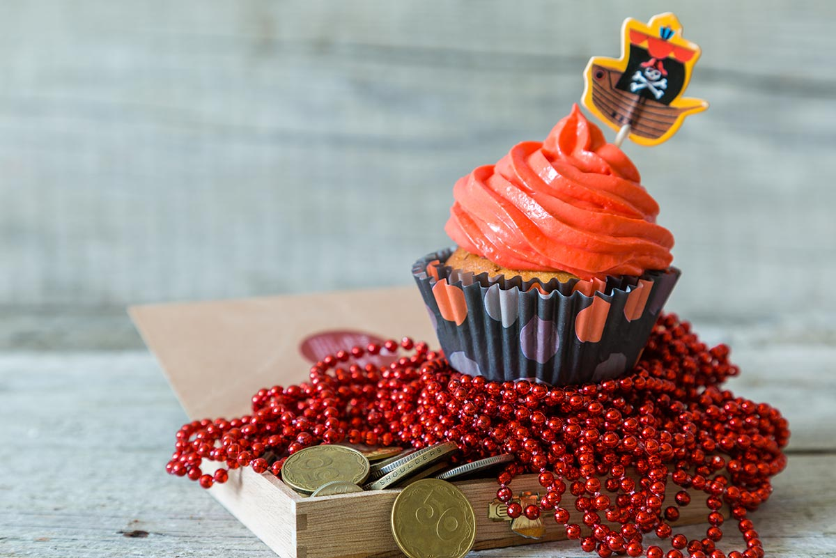 A pirate-themed cupcake: cupcake with orange icing and a pirate ship decoration sitting on an open treasure chest.