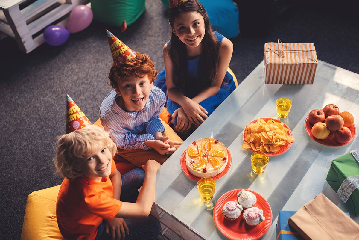 Three kids wearing party hats at around a table smiling and waiting to eat cake.