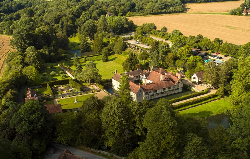Aerial view of Ightham Mote with greenery and trees surrounding house.