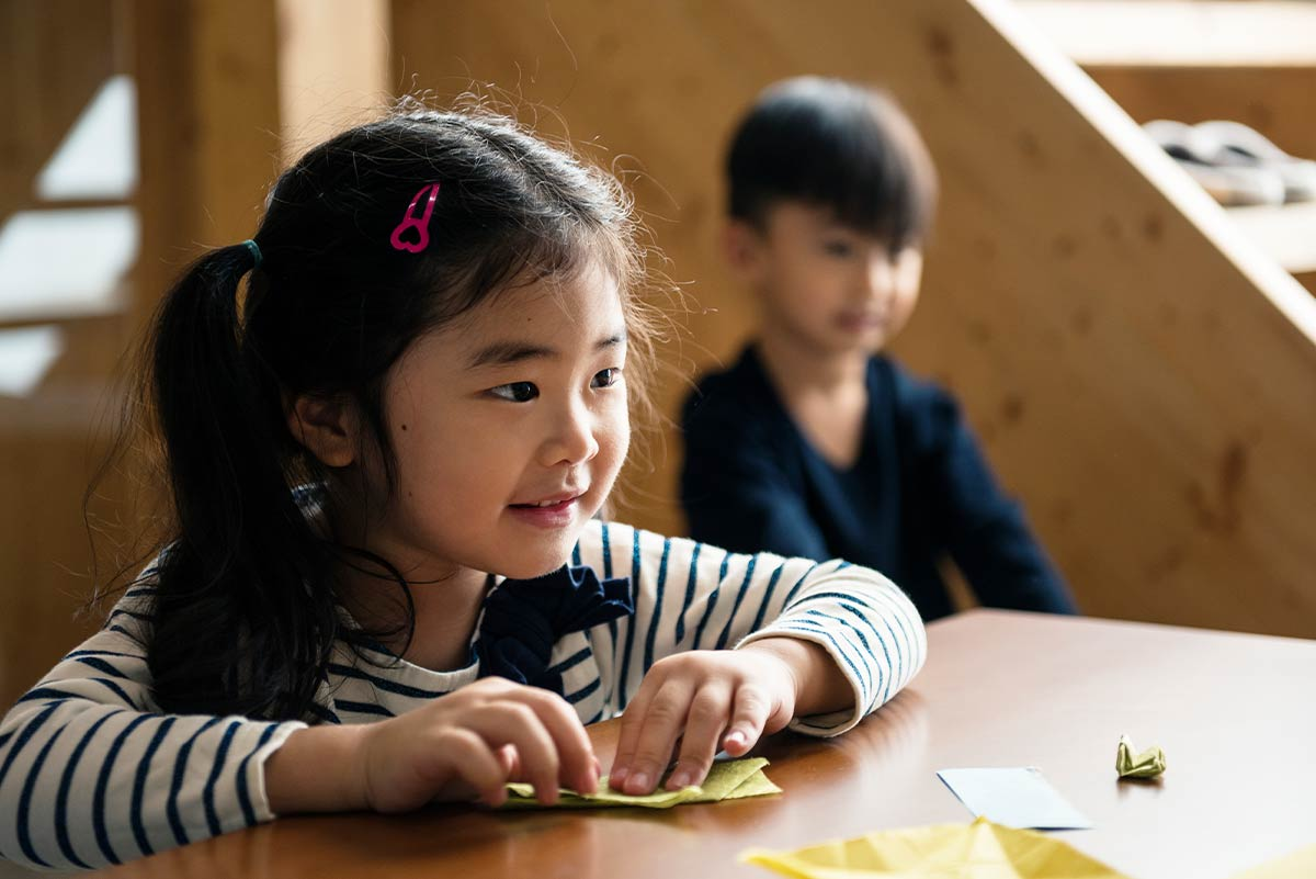 Little girl sat at the table smiling as she folds paper to make an origami squirrel.