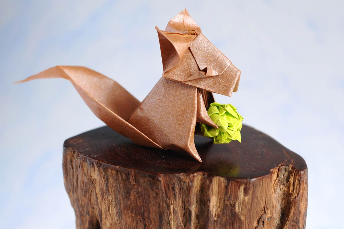 Shimmery brown origami squirrel placed on a polished log holding a green origami acorn.