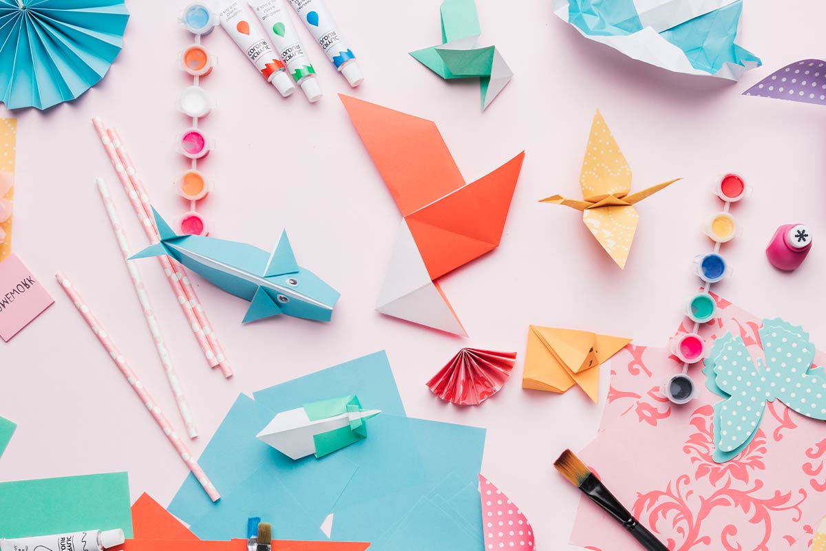 Various origami animals and shapes, already made, places on a pink surface.
