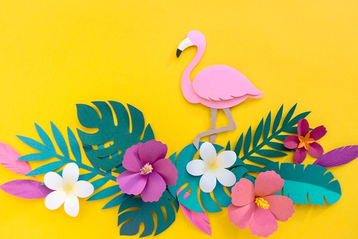 A pink origami flamingo which looks as if it's walking on some origami flowers stuck on a yellow background.