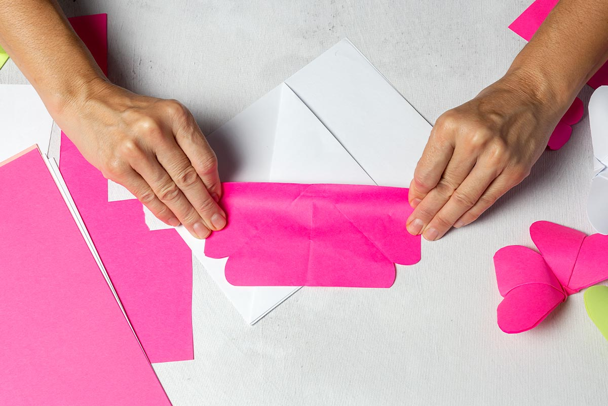 Hands folding down pink paper to make an origami flamingo.