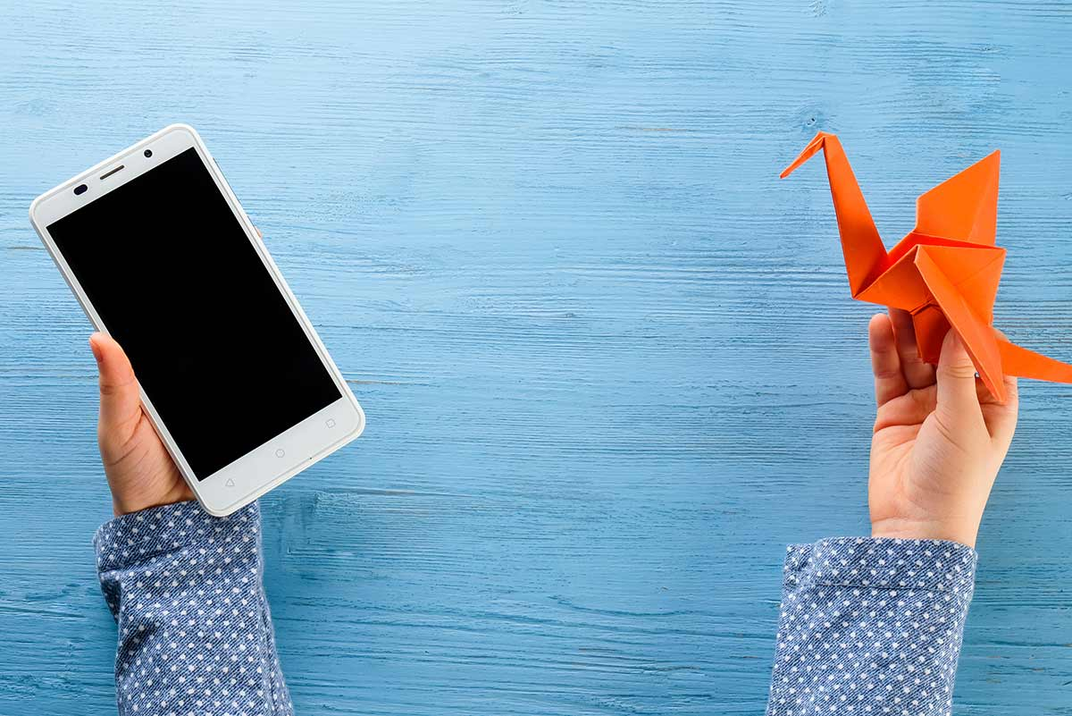 Close up of a child's hands holding an orange origami bird in one and a smartphone in the other.