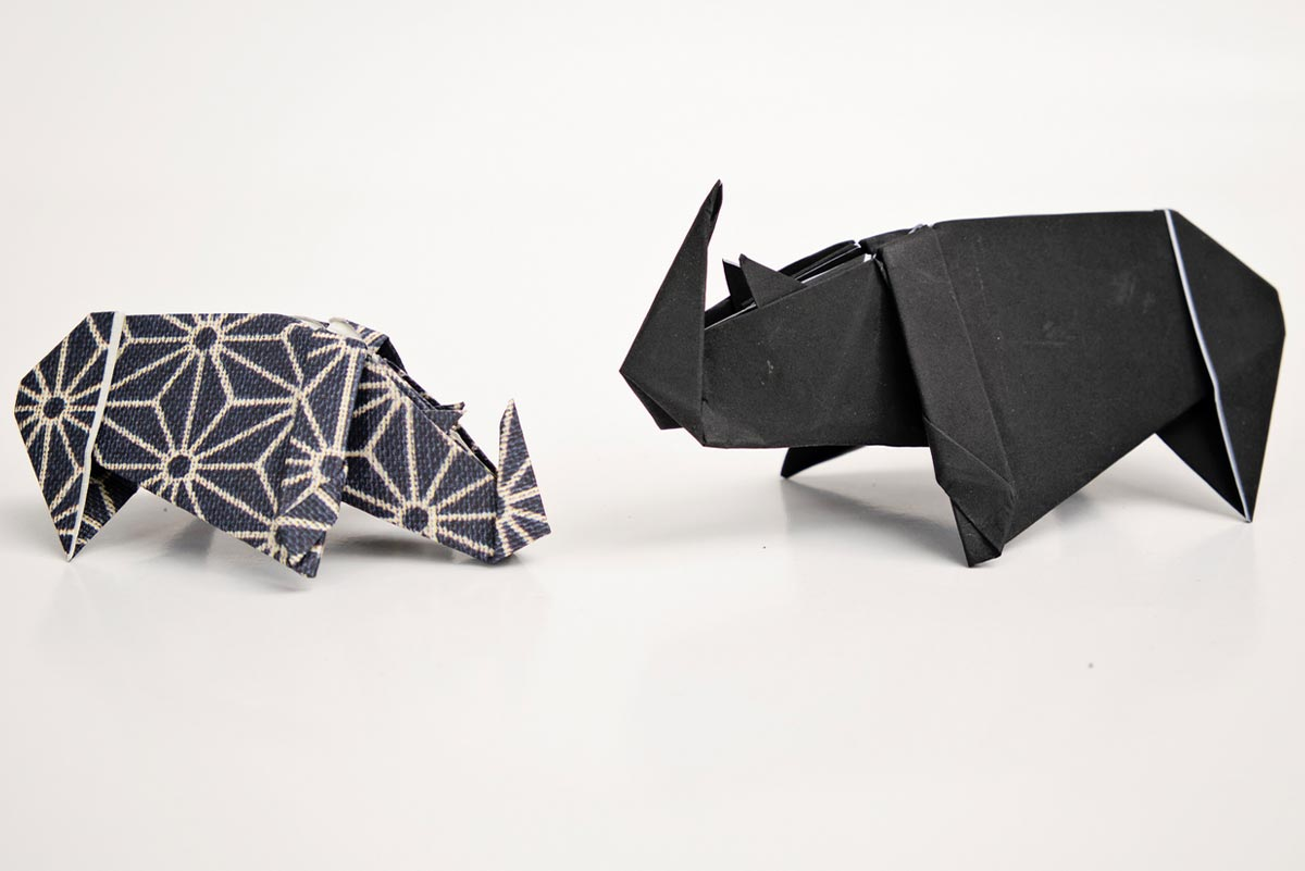Two origami rhinos standing up facing each other as if in the wild.