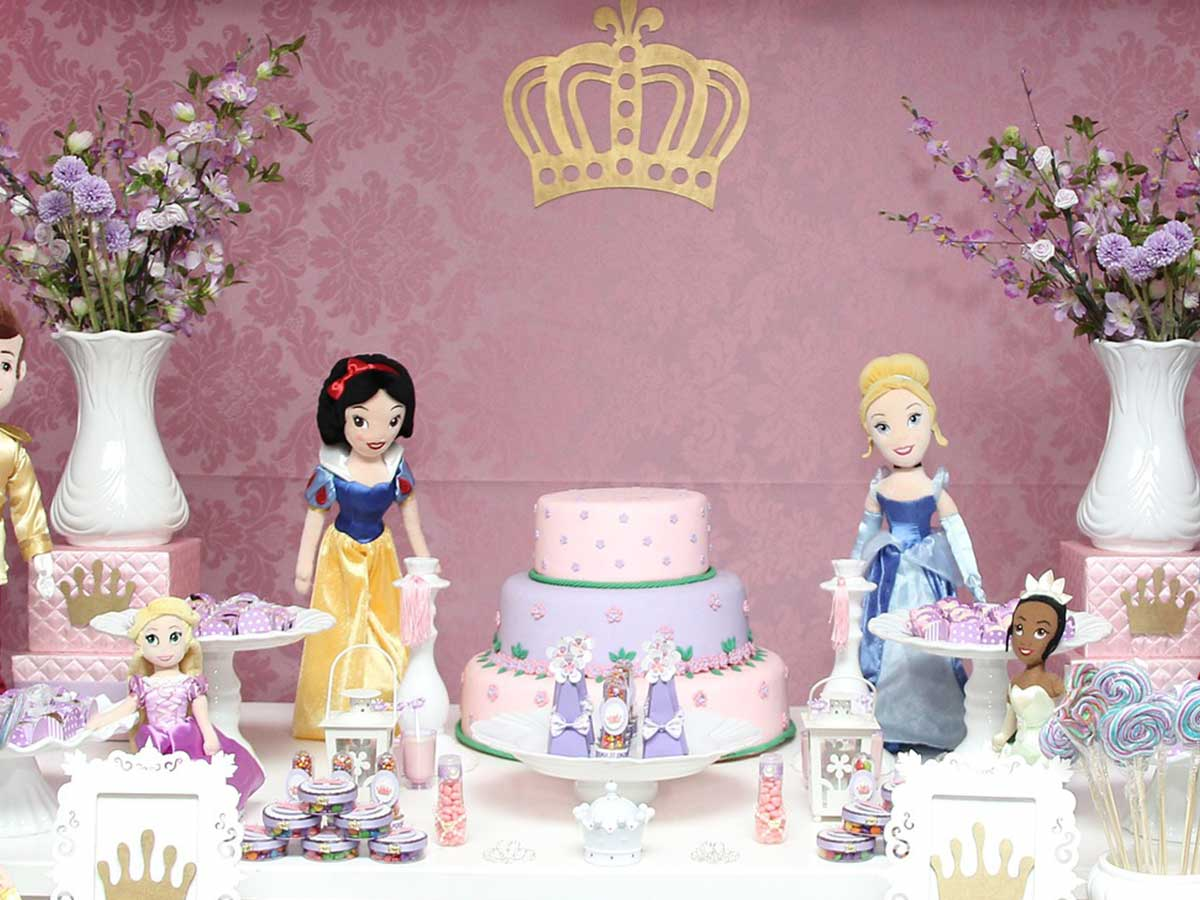 Pink and purple layered princess cake on a display table, surrounded by flowers, Disney princess toys and sweets.