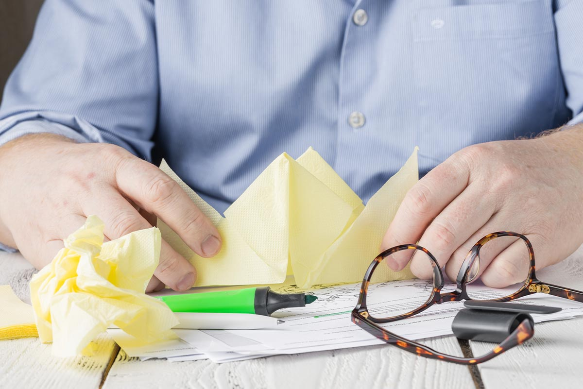Man at table trying to fold an origami rhino that stands up.
