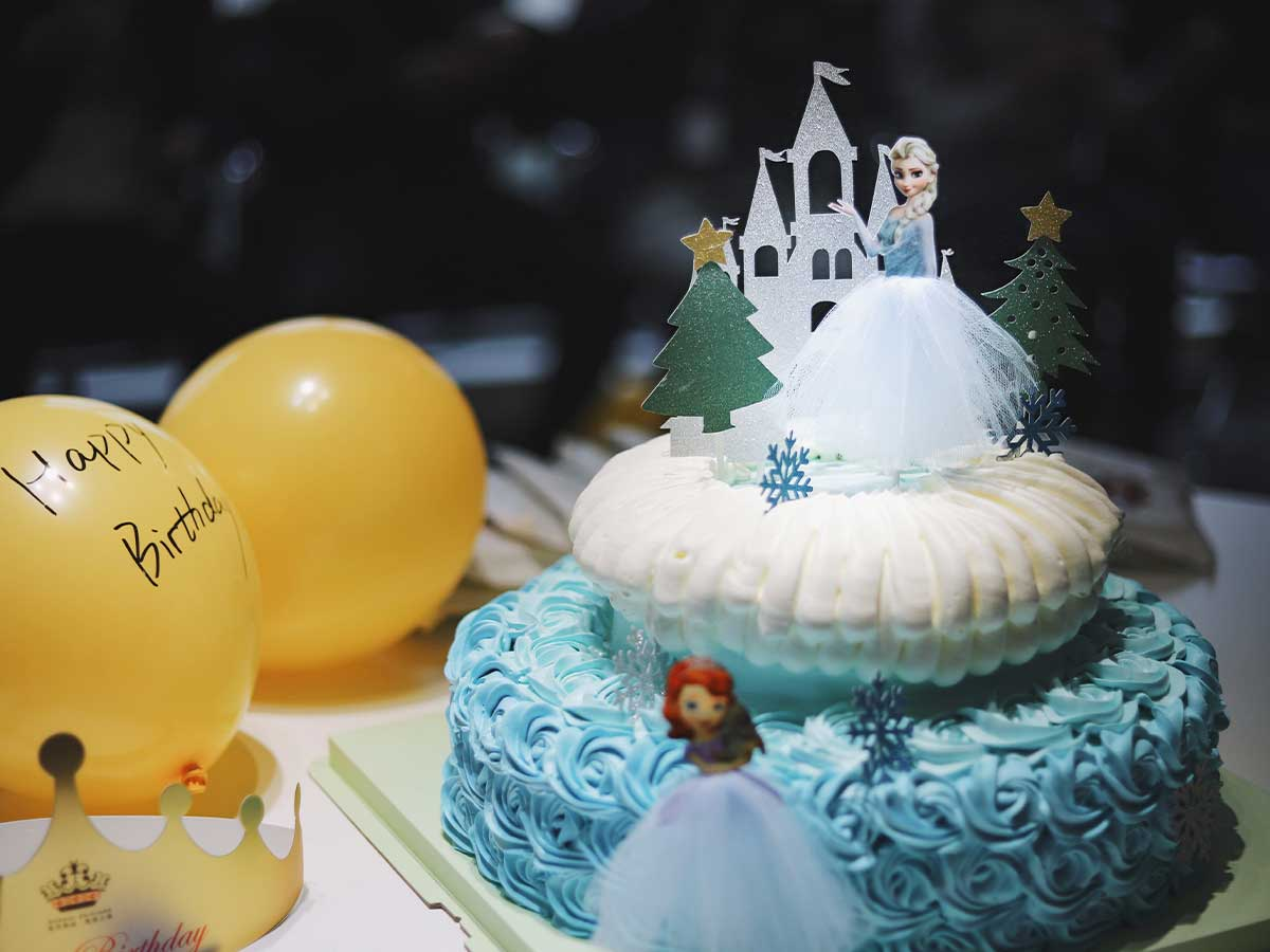 White and blue Frozen themed princess castle cake with Elsa and Anna cake toppers next to some birthday balloons.