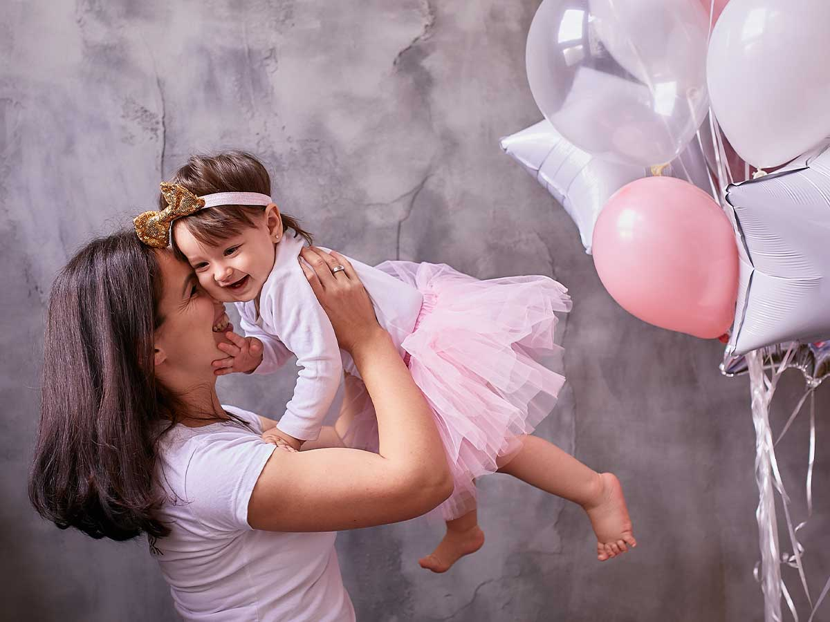 A mother smiles at her daughter as she lifts the toddler above her at a princess party next to some pink balloons.