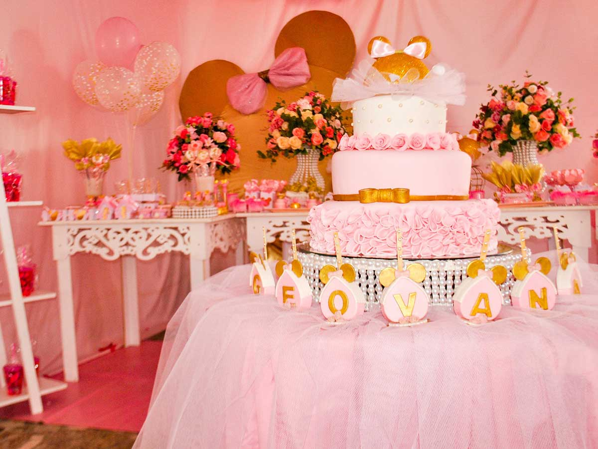 A pink layered princess cake o a display table at a princess party, surrounded by pink flowers, balloons and other decorations.e
