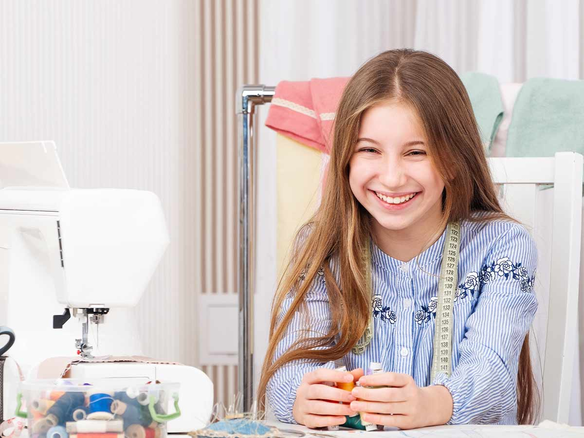 A girl using a sewing machine to make a DIY laptop case and surrounded by sewing equipment, including different coloured threads and a pin cushion, laughs into the camera.