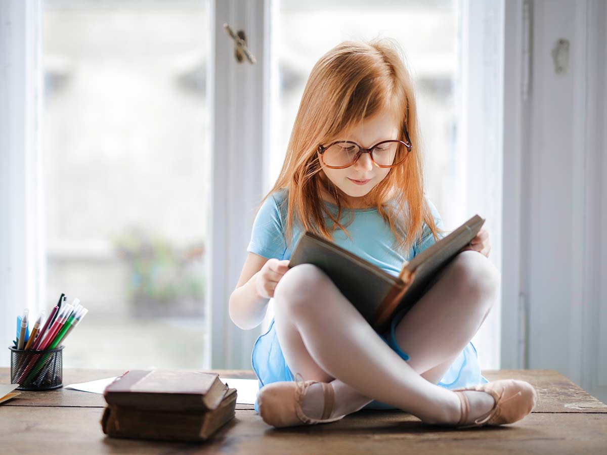 Little girl wearing glasses sat cross-legged on the table reading a book about synonyms and antonyms.